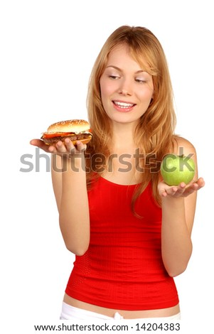 Young woman having a dilemma: greasy hamburger or an apple?