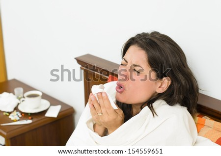 Young woman having a flu and sneezing - stock photo