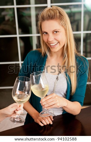 Young woman having a glass of wine with a friend - stock photo