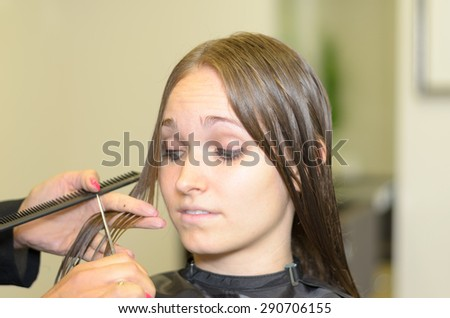 Young woman having a new hairstyle at the hairdresser watching with trepidation as the stylist prepares to cut short one of her long brown locks, close up of her expression and the stylists hand - stock photo