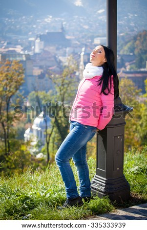 Young woman having a sun bath in autumn. Fashion portrait of pretty girl in cold weather wearing a pink jacket and jeans. - stock photo
