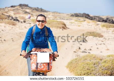 Young woman having a weekend excursion on the bike on a summer day - stock photo