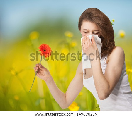 Young woman having allergy staying outdoors in a summer meadow with red herber - stock photo
