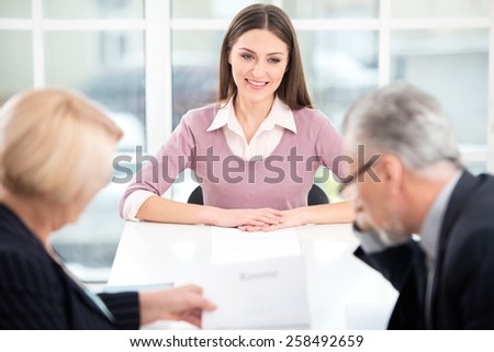 Young woman having an interview or business meeting with employers. Employers examining her CV. Office interior with big window - stock photo