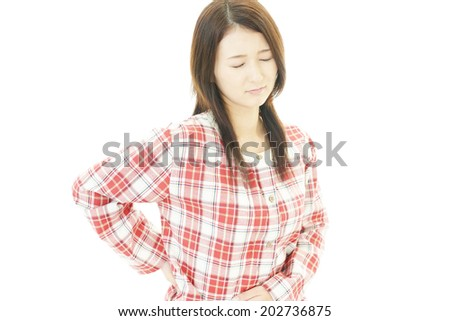 Young woman having back and stomach pain - stock photo