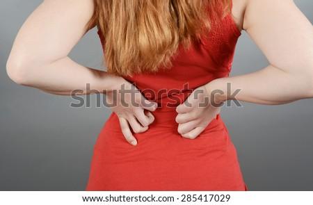 Young woman having back pain, lumbago, sciatica - stock photo