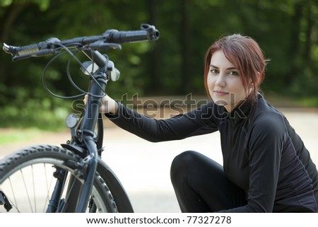 young woman having bike problem in park - stock photo