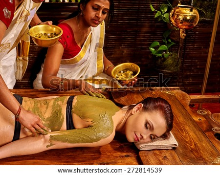 Young woman having body Ayurveda spa massage. Green mud. - stock photo