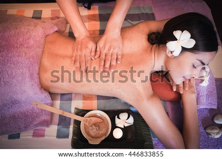 Young woman having body Ayurveda spa massage. Herbal Scrub Spa. Scrub massage body treatment in Thai spa. - stock photo