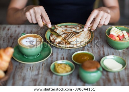 Young woman having breakfast and cut pancakes with golden fork and knife - stock photo