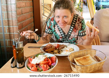 Young woman having breakfast in street cafe - stock photo