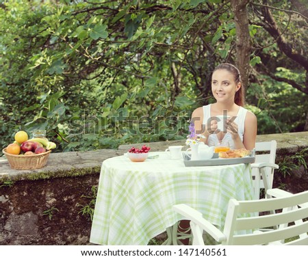 Young woman having breakfast in the garden on a summer day - stock photo