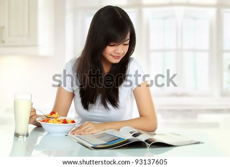 young woman having breakfast while reading magazine - stock photo