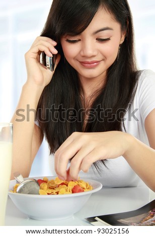 young woman having breakfast while talking on the phone - stock photo