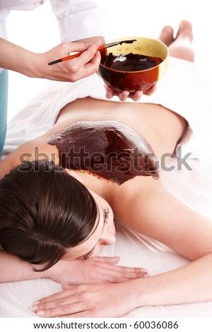 Young woman having chocolate body mask. - stock photo