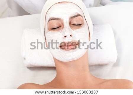 Young woman having facial mask on, laying eyes closed. - stock photo