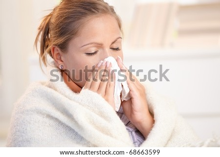 Young woman having flu, feeling bad, blowing her nose, wrapped up in blanket.? - stock photo