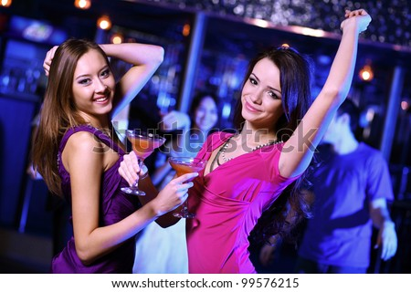 Young woman having fun and dancing at night club disco