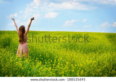 Young woman having fun at canola field - stock photo