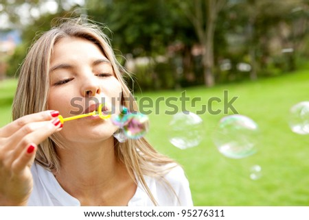 Young woman having fun blowing bubbles at the park - stock photo