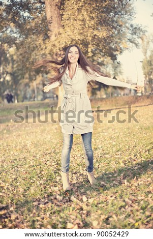 young woman having fun in autumn park, vintage style