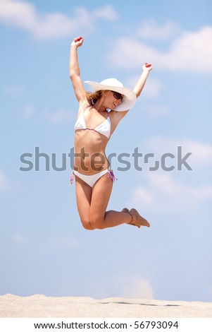 Young woman having fun on a beach. Jumping - stock photo