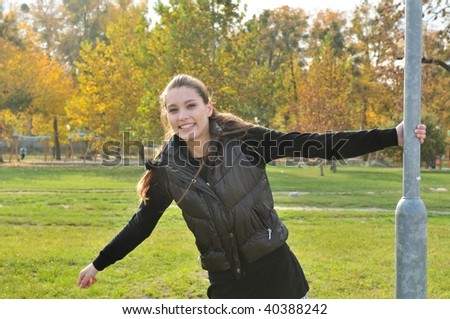 Young woman having fun outdoors in fall time - trees in background
