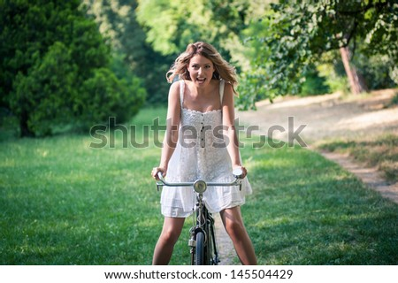 Young woman having fun riding a bicycle in the park. - stock photo