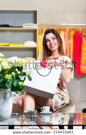 Young woman having fun while fashion shopping in boutique or store and showing a garment