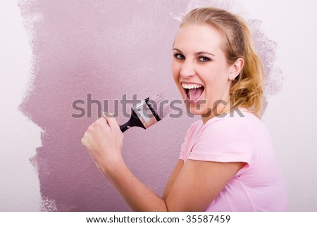 young woman having fun while painting home - stock photo