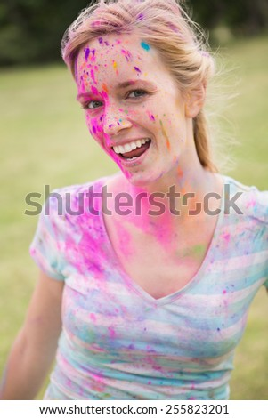 Young woman having fun with powder paint on a sunny day - stock photo