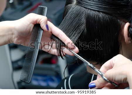 young woman having her hair being cut - stock photo
