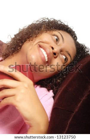 Young woman having her morning cup of coffee on the couch and laughing - stock photo