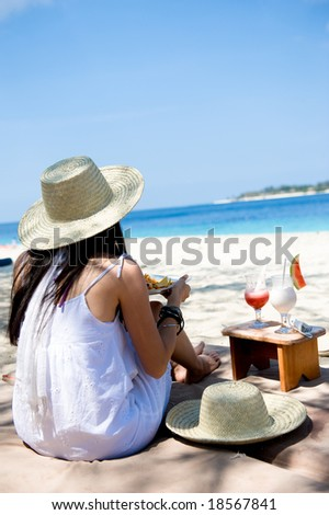young woman having her snack by the beach - stock photo