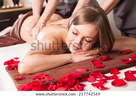 Young woman having massage in beauty spa by two therapist - stock photo