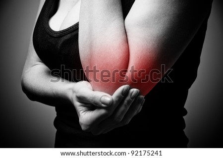 young woman having pain in her elbow - stock photo