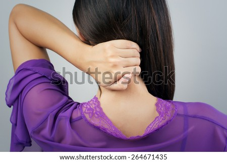 Young woman having pain in the back and neck, Pain in the back - stock photo