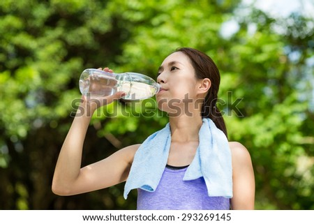 Young woman having rest after sport exercises holding bottle of water  - stock photo