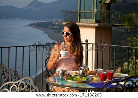 Young woman having romantic breakfast in sunrise at resort restaurant outdoor. Healthy food drink for breakfast. Beautiful woman at vacation in Sicily. - stock photo