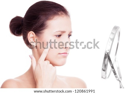 young woman having skin problems, looking into the mirror isolated against white background - stock photo