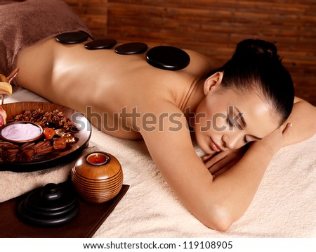 Young woman having stone massage in spa salon. Healthy lifestyle. - stock photo