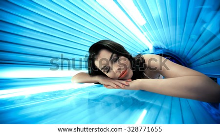 Young woman  having tanning skin treatment in solarium - stock photo