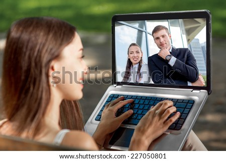 Young woman having video call with her business friends on laptop at the park - stock photo