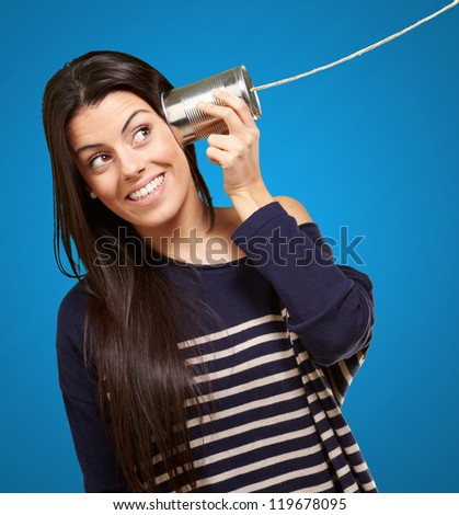 Young woman hearing using a metal tin can over blue background - stock photo