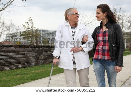 Young woman helping a senior woman - stock photo