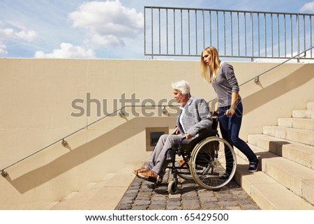 Young woman helping an elderly woman in wheelchair - stock photo