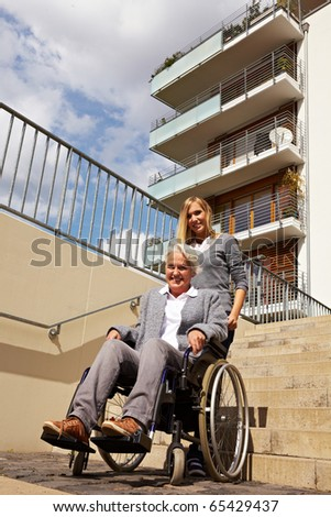 Young woman helping an elderly woman in wheelchair with staircase - stock photo