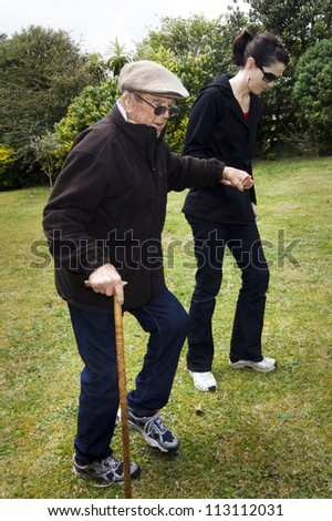 Young woman helping and supporting her grandfather to walk outdoor in the garden with his support walking stick.Concept photo of old age, health care,lifestyle, pensioner,medical, retirement.  - stock photo