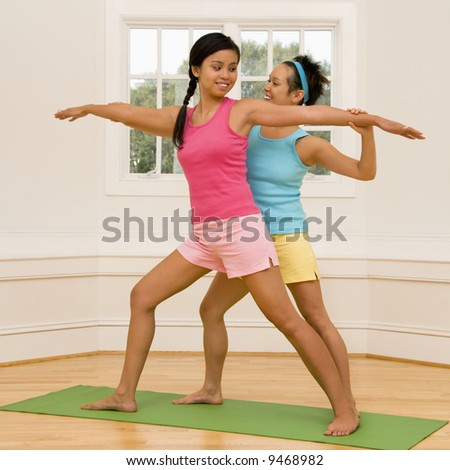 Young woman helping another young woman with positioning on her yoga pose. - stock photo