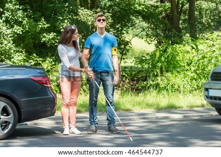 Young Woman Helping Blind Man Wearing Stock Photo